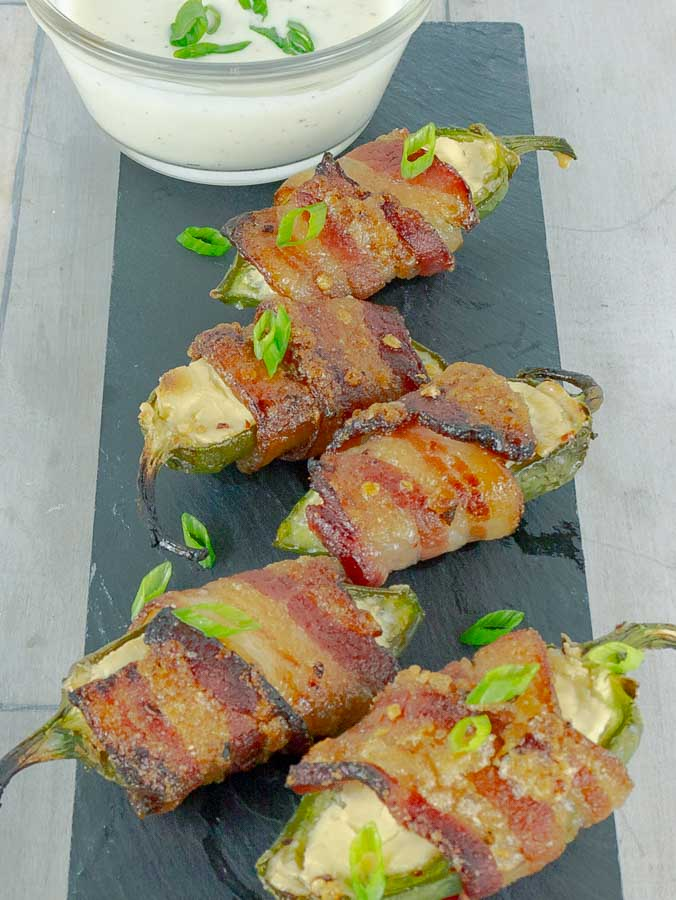 five Bourbon Candied Bacon Wrapped Jalapeno Poppers on a piece of slate with ranch