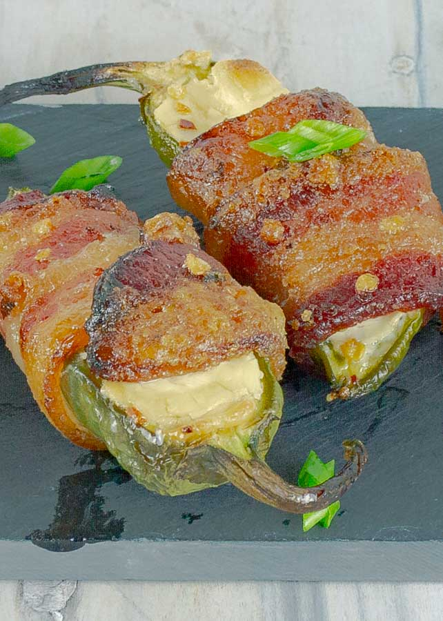 two Bourbon Candied Bacon Wrapped Jalapeno Poppers on black slate