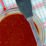 Homemade Chipotle Brown Sugar Barbecue Sauce in clear bowl with plaid napkin