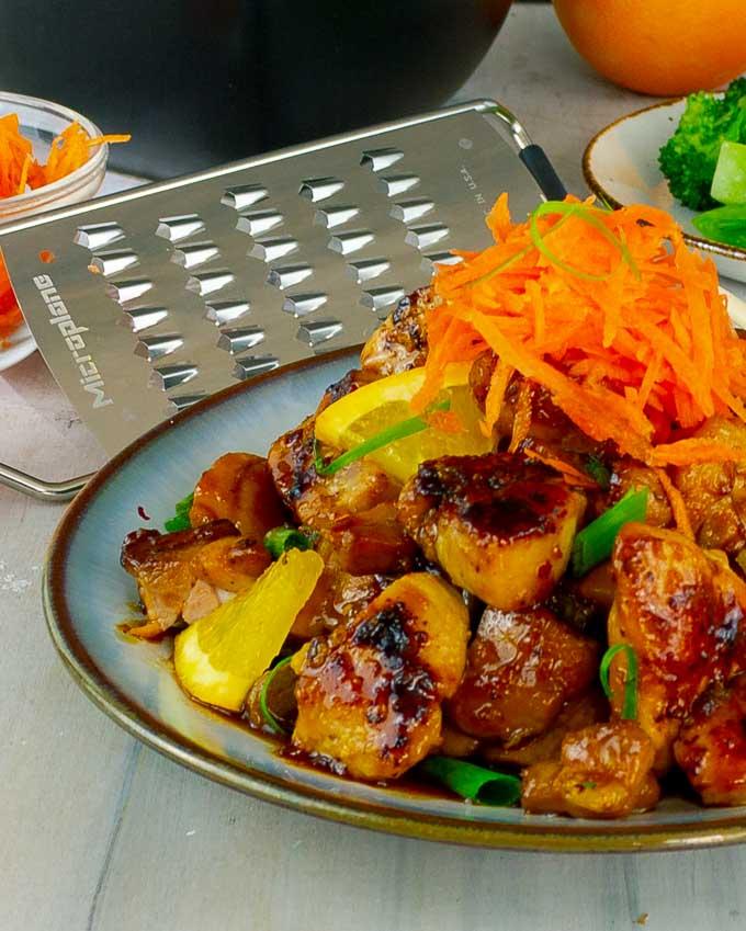 plate of Sticky Orange Chicken Recipe with a carrot garnish