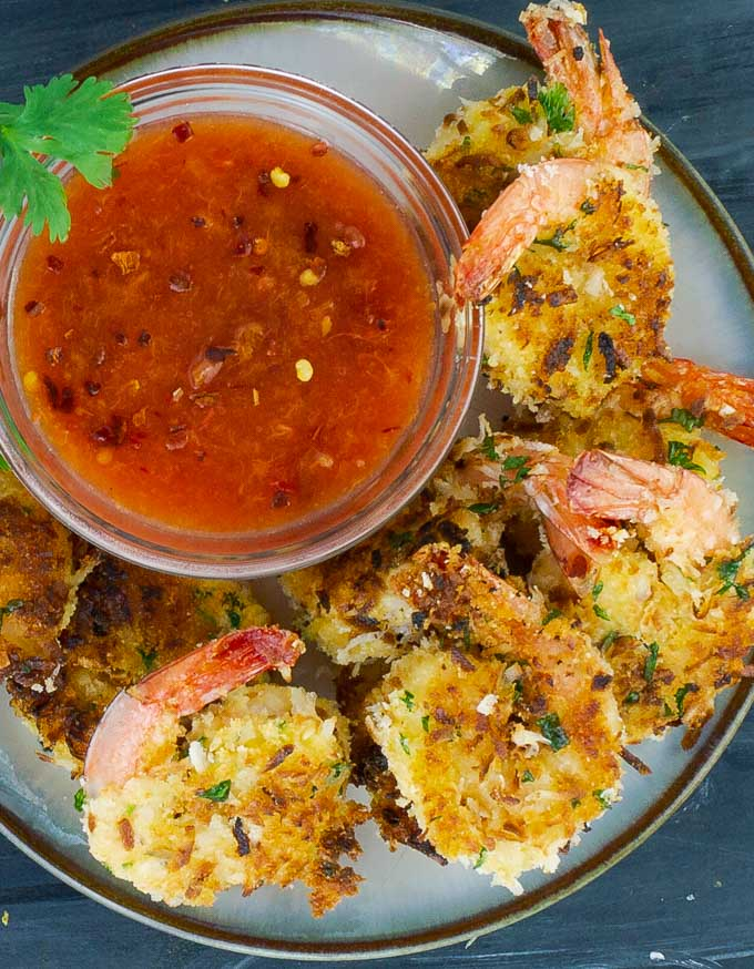 a white plate of Coconut Shrimp with a bowl of Peach Sweet and Spicy Chili Sauce