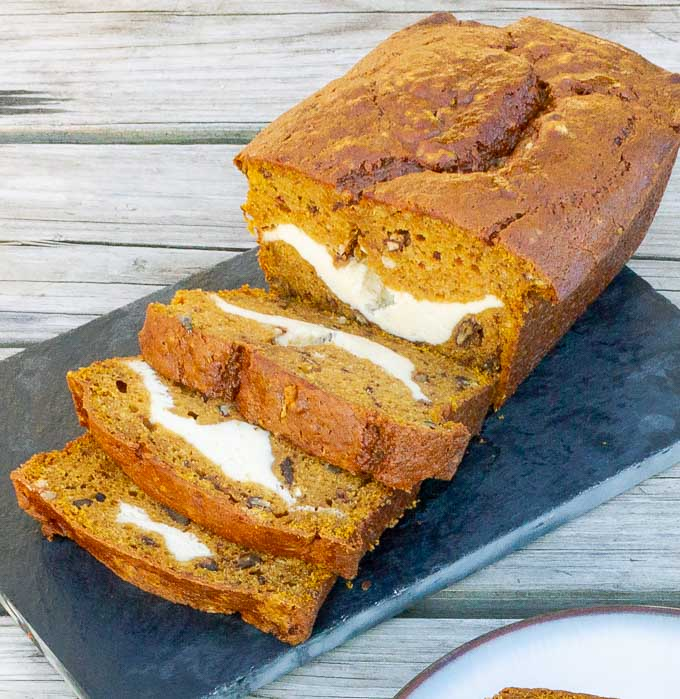 Slices of Cream Cheese Stuffed Pumpkin Bread on a cutting board