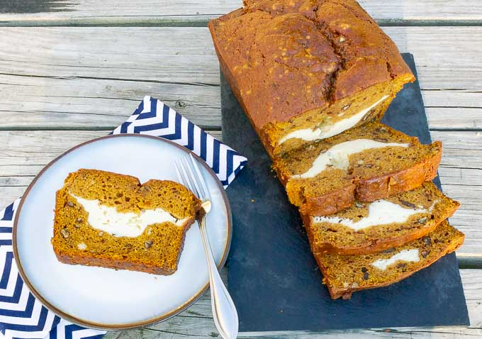 Slices of Cream Cheese Stuffed Pumpkin Bread on cutting board with a slice on a plate