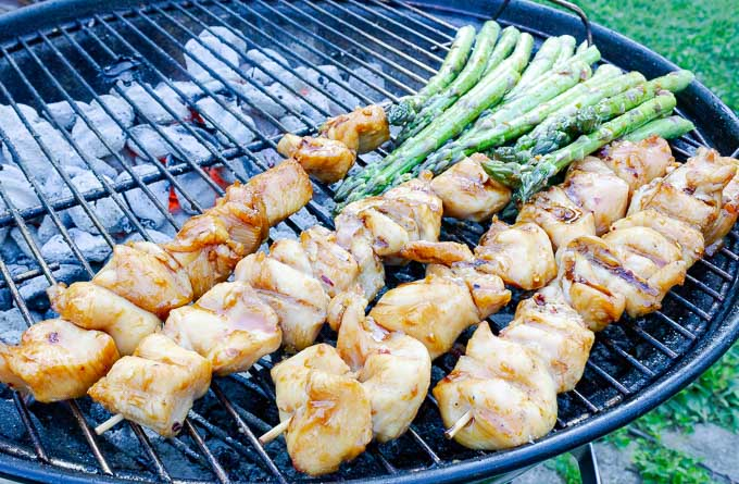 four Grilled Asian Chicken Kabobs on the grill with asparagus
