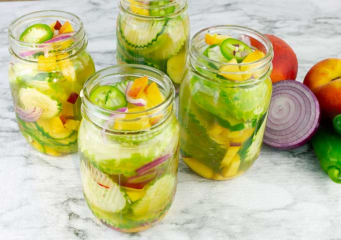 horizontal image of 4 jars of Sweet and Spicy Peach Jalapeno Pickles