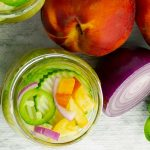 top of a jar of Sweet and Spicy Peach Jalapeno Pickles plus fresh produce