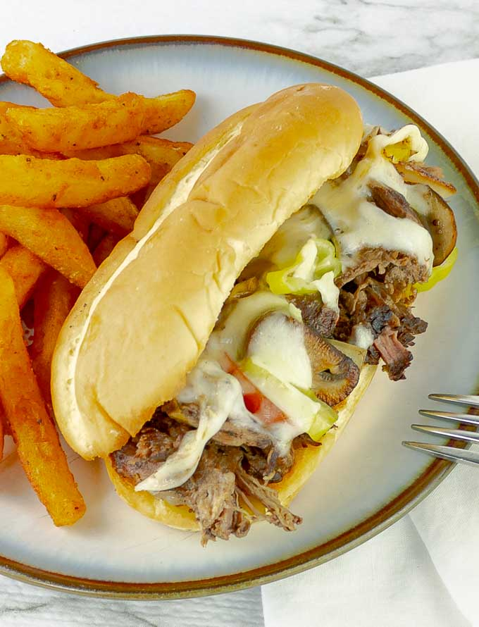 Slow cooker Philly cheese steak sandwich on white plate with fries