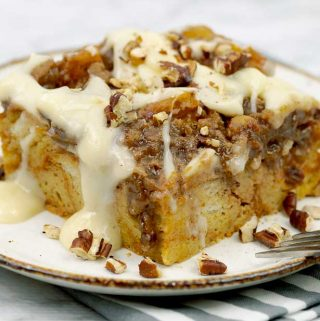 a slice of Pumpkin Pecan Custard Bread Pudding on a white place with frosting drizzle