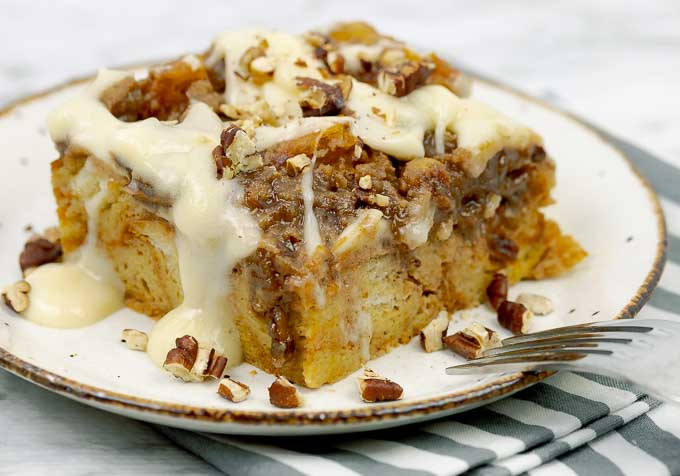 Slice of Pumpkin Pecan Custard Bread Pudding on a white plate