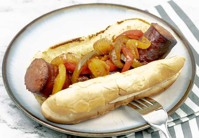 a Sheet Pan Polish Sausage Sandwich on a white plate with onions and peppers and a fork