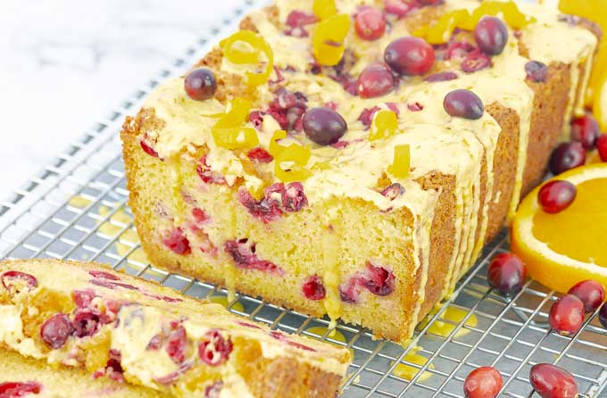 Orange Cranberry Pound Cake sliced open with drizzling glaze on wire rack