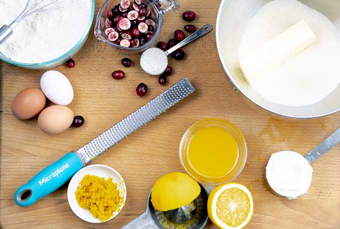 ingredients for Orange cranberry pound cake being prepared on a wooden cutting board