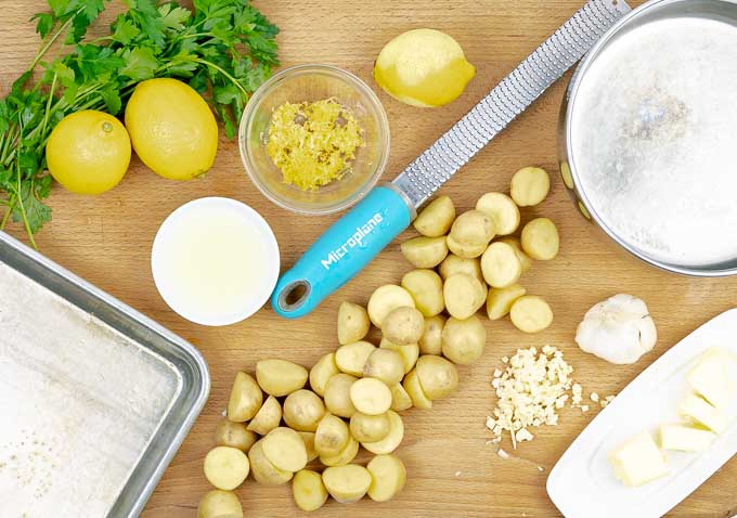 Ingredients for Roasted Lemon Butter Parsley Potatoes being prepared on a wooden cutting board