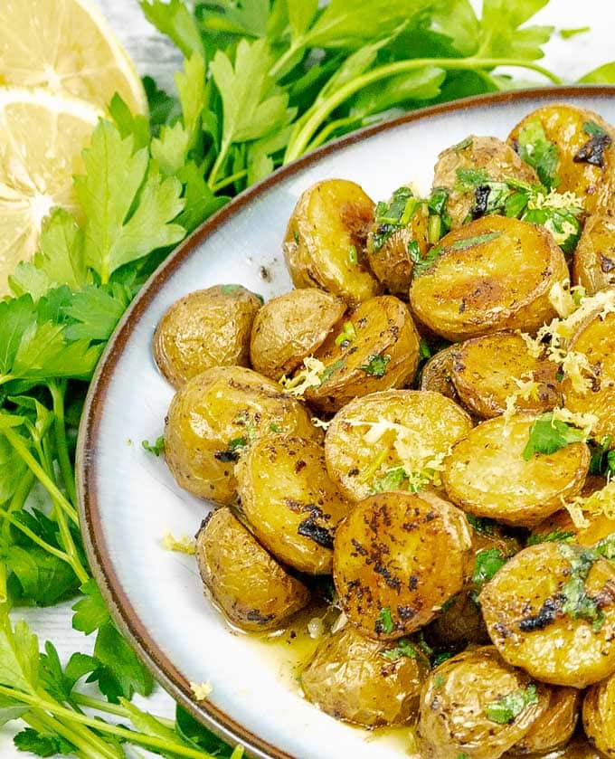 Roasted Lemon Parsley Butter Potatoes on a white plate with parsley and lemon slices