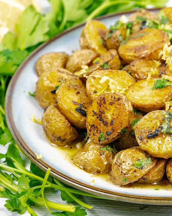 Roasted Lemon Parsley Butter Potatoes with fresh parsley on white plate