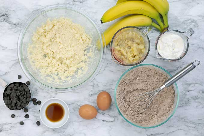 bowl of wet ingredients and bowl of dry ingredients being prepared for double chocolate banana muffins