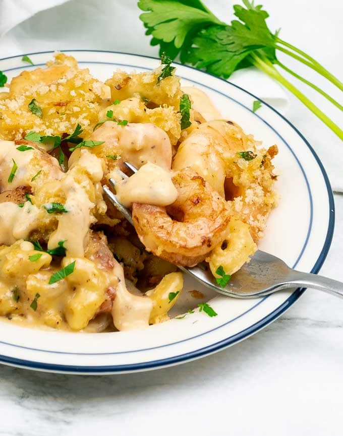 Baked Shrimp Macaroni and Cheese on a white plate with fork tines