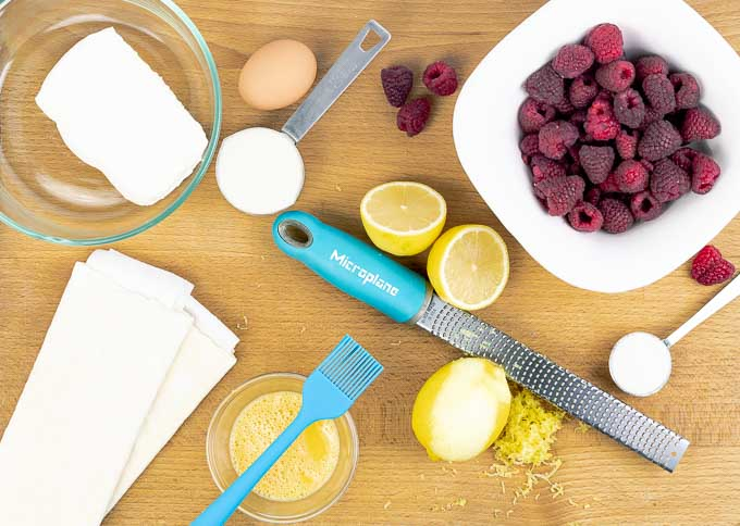 ingredients on a wooden cutting board for raspberry puff pastry tarts with lemon cream cheese