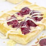 one raspberry puff pastry tarts with lemon cream cheese and drizzle shown up close