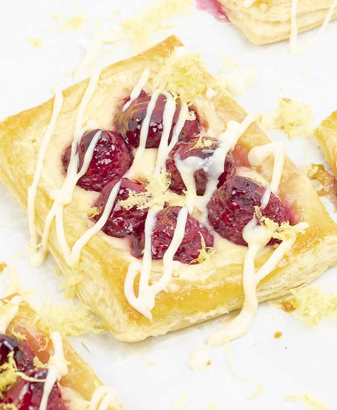 close up of a Raspberry Puff Pastry Tarts with Lemon Cream Cheese drizzle