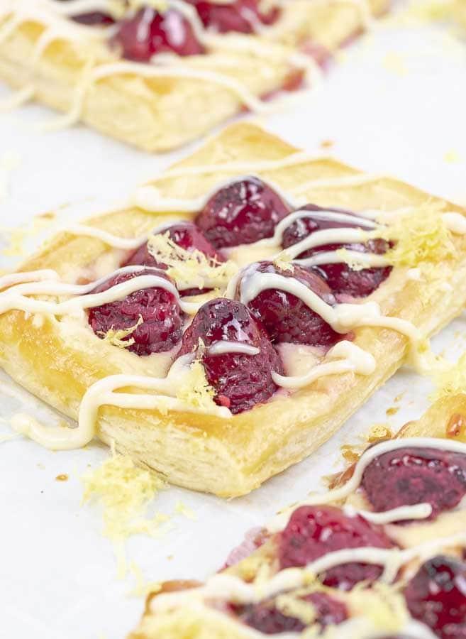 three raspberry puff pastry tarts with lemon cream cheese