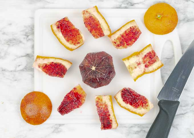 Demonstrating how to slice a blood orange on white cutting board