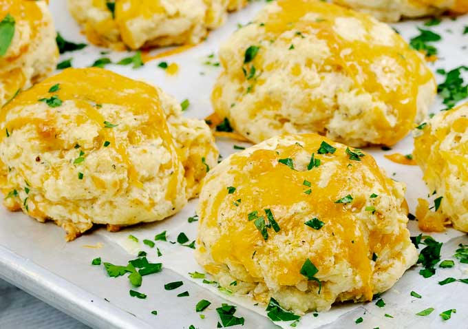 Italian Herb Garlic Cheddar Biscuits From Scratch on metal baking sheet and parchment paper