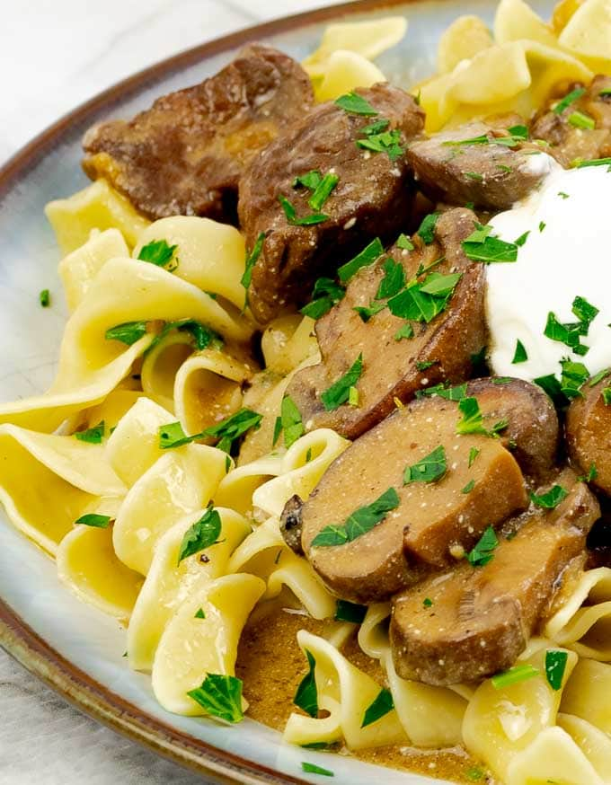 plate of Slow Cooker Beef Stroganoff Recipe From Scratch with a dollop of sour cream