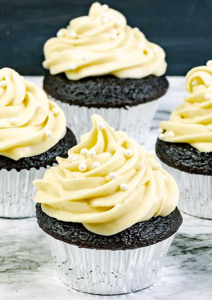 four Guinness Dark Chocolate Cupcakes with Irish Cream Cream Cheese Frosting in silver wrappers