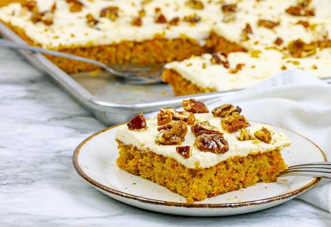 A piece of easy carrot sheet cake recipe from scratch on a white plate.