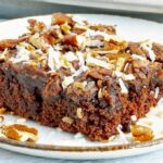 close up of a piece of german chocolate sheet cake on a white plate