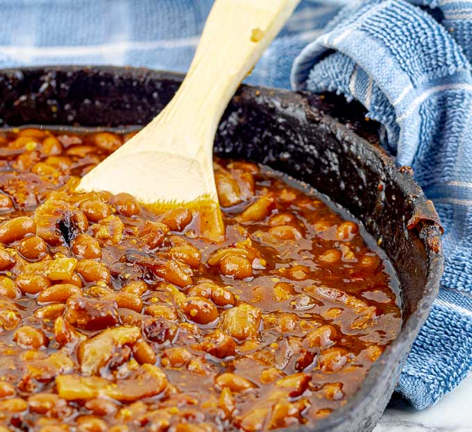 Bourbon Bacon Grilled Baked Beans in a cast iron skillet with a wooden spoon and blue towel