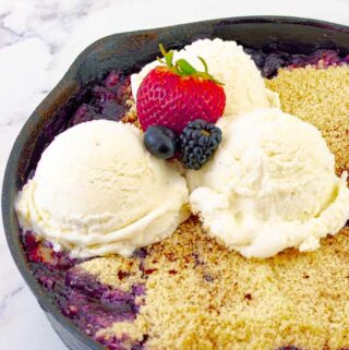 Grilled Triple Berry Crisp in a Cast Iron Skillet with three scoops of ice cream and berries