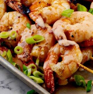 Grilled Bang Bang Shrimp skewers on metal tray with green onion slices