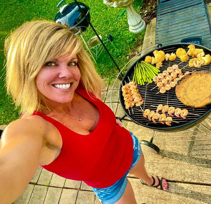 Jennifer next to a barbecue grill making grilled cauliflower