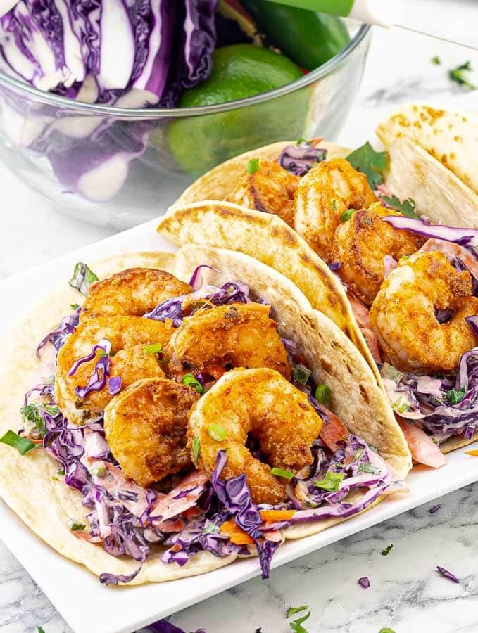two cajun shrimp tacos on a white platter
