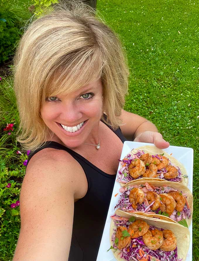 Jennifer holding a white platter with three tacos