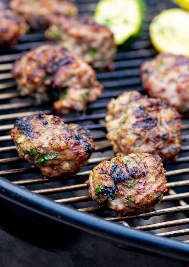 two grilled homemade Italian meatballs in the front on the grill