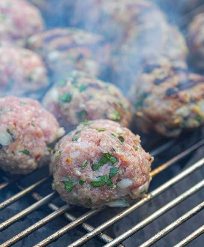 raw meatballs just placed on the grill