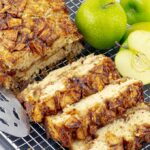 Apple cinnamon swirl loaf on wire rack with three pieces cut
