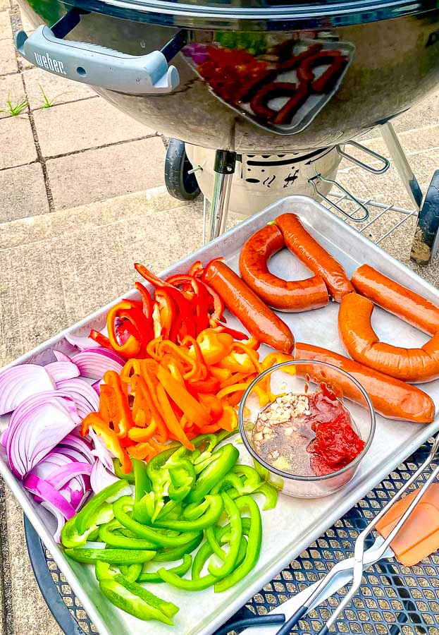 ingredients for grilled sausage with onions and peppers next to a weber grill