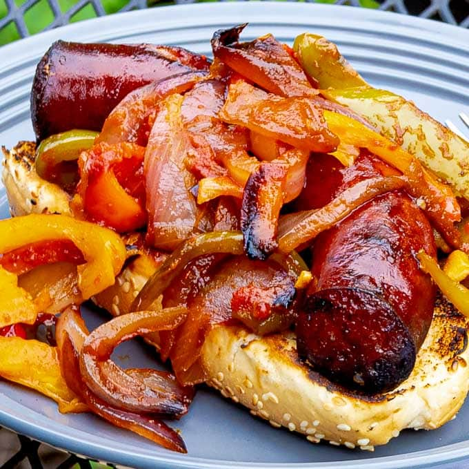 Grilled Sausage with Peppers and Onions on a bun on a gray plate