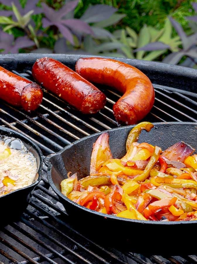 sausages and a cast iron skillet of onions and peppers on the grill